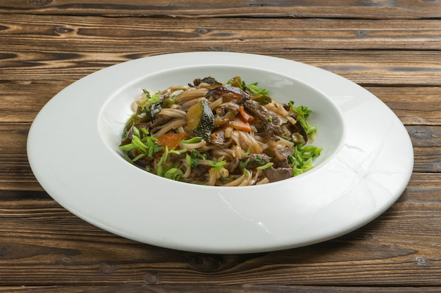 Chinese rice noodles wok with beef, vegetables and green onions.
