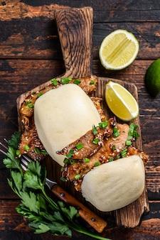 Китайский сэндвич, приготовленные на пару булочки из гуабао со свининой. черный фон. вид сверху.
