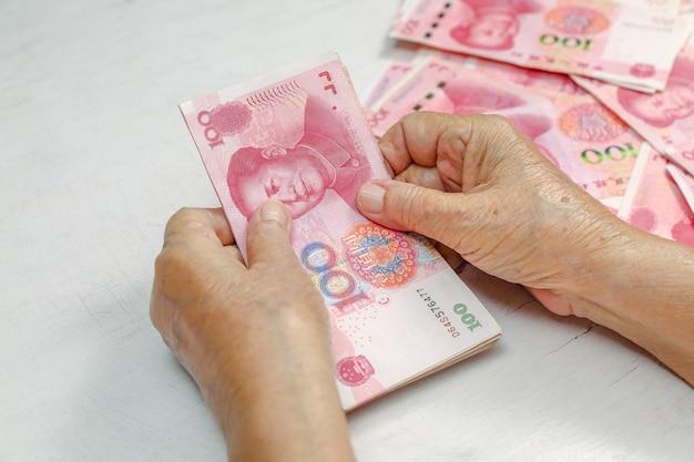 Китайская старшая женщина, считающая деньги для оплаты Premium Фотографии