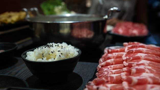 중국식 매운 전골 수프. 대만의 한 레스토랑 테이블에 돼지고기와 쇠고기의 생고기 슬라이드가 있는 접시와 밥그릇이 있습니다. 신선하고 맛있는 요리를 선보이는 대표적인 전골 한방 요리