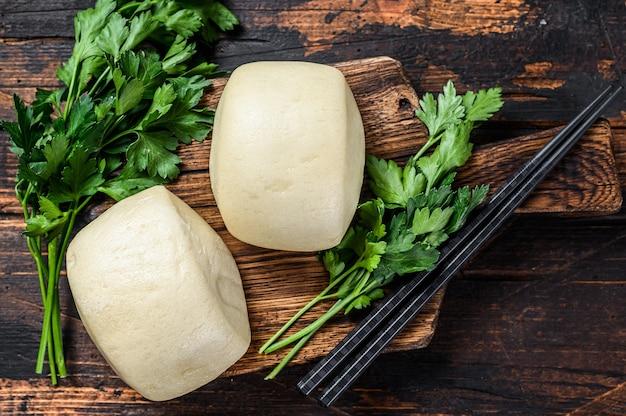 Китайские паровые булочки бао. темный деревянный фон. вид сверху.