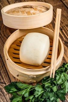 Китайские булочки на пару в традиционном бамбуковом пароварке. деревянный фон. вид сверху.