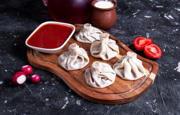 Chinese steamed buns with red sauce on the wooden board