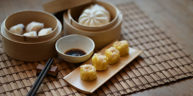 Chinese steamed dumpling and steamed pork bun in a bamboo steamer with chopstick on wooden table