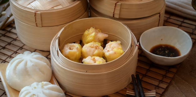 Chinese steamed dumpling and steamed pork bun in a bamboo steamer with chopstick