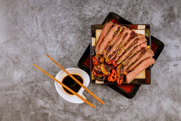 Chinese style sliced roast beef steak mushrooms sesame seeds, soy sauce with chopsticks