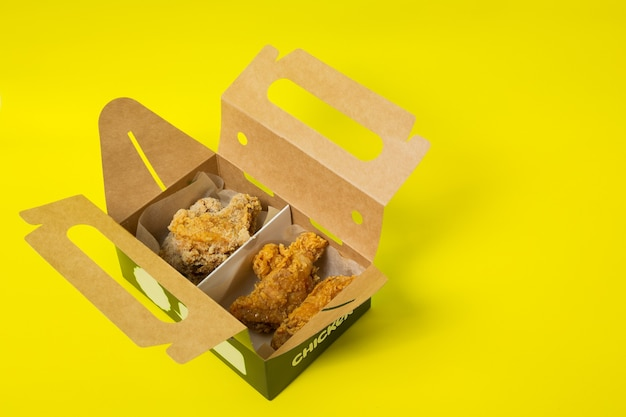 Chinese takeaway chicken with tomatoes in a cardboard box photographed on a yellow background