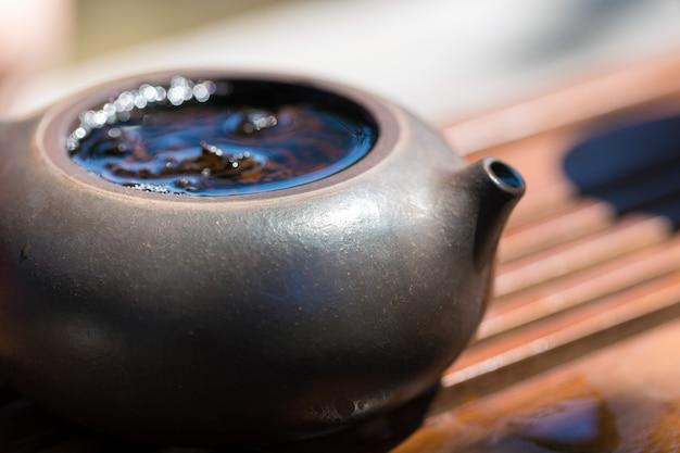 Китайская чайная церемония. керамический чайник из глины и чаш на деревянном фоне.