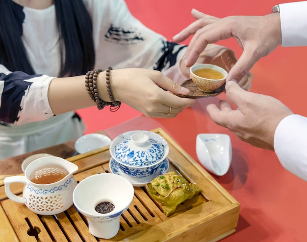 Chinese tea ceremony. the girl pours the tea from the kettle into the cup.