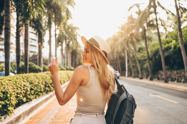 Premium Photo   Chinese tourist walking in city streets on asia vacation tourism. caucasian beautiful woman in hat with backpack travel lifestyle concept. walking street, green palms and highway in sanya, hainan.
