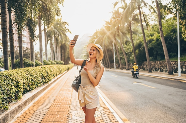 Chinese tourist walking in city streets on asia vacation tourism. caucasian beautiful woman with backpack taking selfie smartphone. travel lifestyle concept. green palms and highway in sanya, hainan.