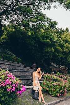 Chinese tourist walking and discovering nature on asia vacation tourism. caucasian beautiful woman with backpack.  travel lifestyle concept. sanya, hainan, china. tropical landscape with green trees