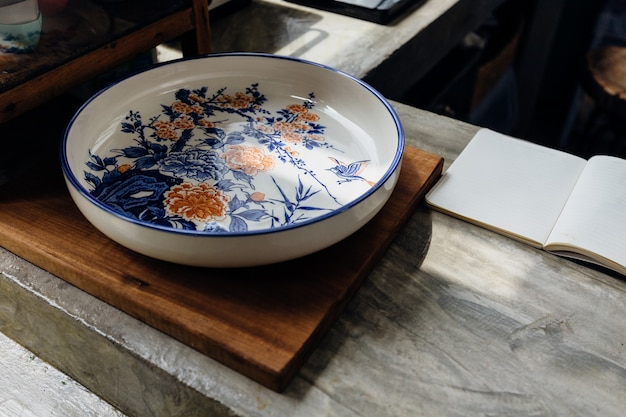 Chinese traditional decorative ceramic plate on wooden block with open notebook on kitchen counter.