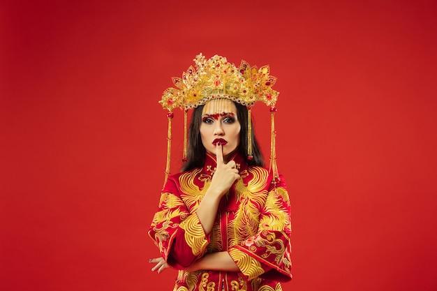 赤い背景の上のスタジオで中国の伝統的な優雅な女性。民族衣装を着た美少女。中国の旧正月、優雅さ、優雅さ、パフォーマー、パフォーマンス、ダンス、女優、ドレスのコンセプト