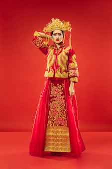 빨간색 배경 위에 스튜디오에서 중국 전통 우아한 여자. 민족 의상을 입고 아름 다운 소녀입니다. 구정, 우아함, 은혜, 연기자, 공연, 춤, 배우, 드레스 컨셉