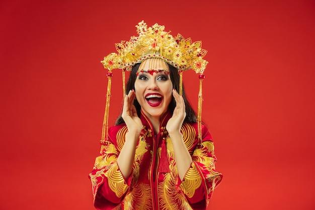 빨간색 배경 위에 스튜디오에서 중국 전통 우아한 여자. 민족 의상을 입고 아름 다운 소녀입니다. 구정, 우아함, 은혜, 연기자, 공연, 춤, 배우, 감정 개념