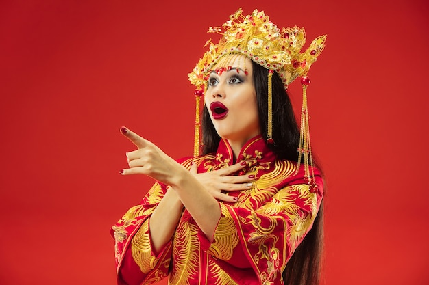赤い背景の上のスタジオで中国の伝統的な優雅な女性。