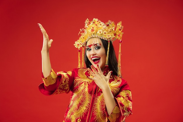 붉은 벽에 스튜디오에서 중국 전통 우아한 여자