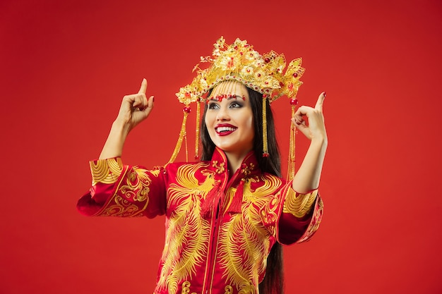 Китайская традиционная изящная женщина в студии над красным.