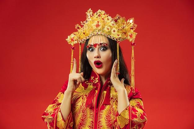 Donna graziosa tradizionale cinese in studio su sfondo rosso. bella ragazza che indossa il costume nazionale. capodanno cinese, eleganza, grazia, performer, performance, danza, attrice, concetto di abbigliamento