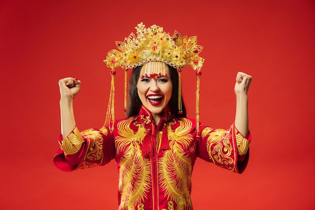 Chinese traditional graceful woman at studio over red background. beautiful girl wearing national costume. chinese new year, elegance, grace, performer, performance, dance, actress, dress concept