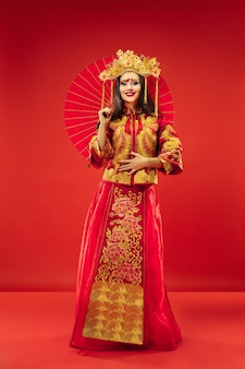 Chinese traditional graceful woman at studio over red background.