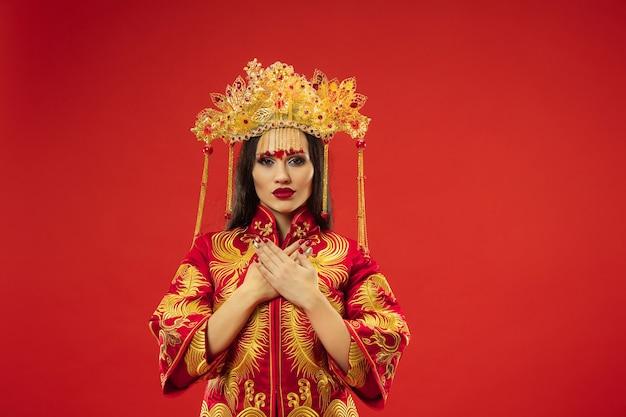 Donna graziosa tradizionale cinese allo studio sopra la parete rossa