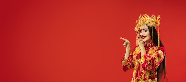 Chinese traditional graceful woman at studio over red wall