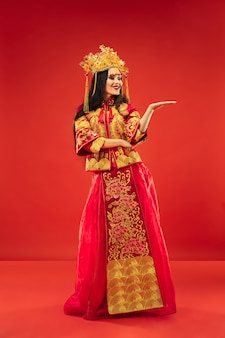 Chinese traditional graceful woman at studio over red.
