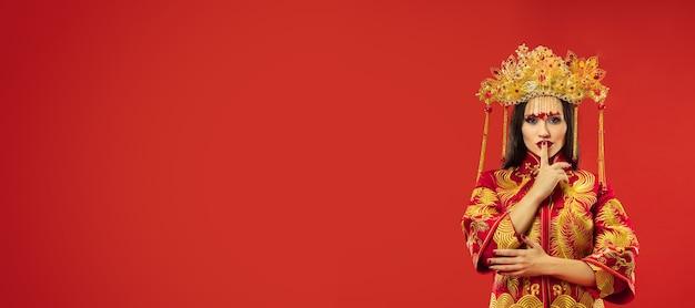 Donna graziosa tradizionale cinese allo studio sopra il rosso.