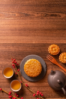 Chinese traditional pastry moon cake mooncake with tea cups on bamboo serving tray on wooden background for mid-autumn festival, top view, flat lay