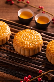Chinese traditional pastry moon cake mooncake with tea cups on bamboo servingwarning tray on wooden background for mid-autumn festival, close up
