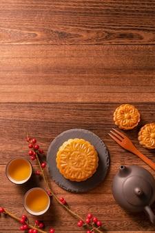 中国の伝統的なペストリー ムーン ケーキ ムーンケーキ中秋節、トップ ビュー、フラット レイアウトの木製の背景に竹のサービング トレイにティー カップ
