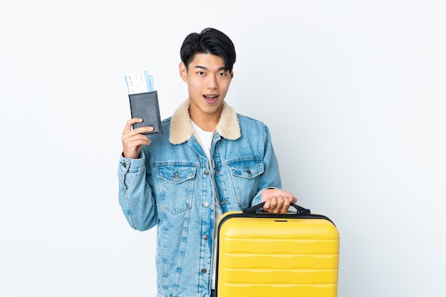 Chinese over in vacation with suitcase and passport