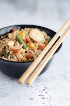 Chinese vegetable fried rice and eggs served in a bowl with chopsticks. chinese cuisine