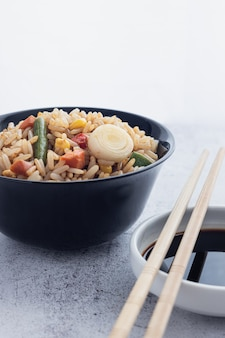 Chinese vegetable fried rice and eggs served in a bowl with chopsticks and sauce soy. chinese cuisine