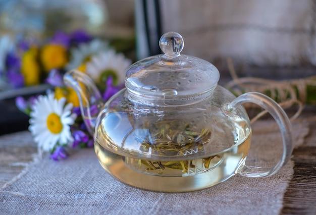 フィールドの花と鏡と木製のテーブルの上のガラスのティーポットで資金調達州からの中国の白茶