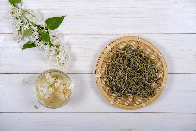 竹皿と木製の背景に白いライラックの花の中国の白茶