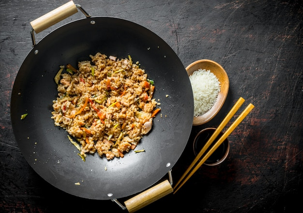 Chinese wok. cooked rice in a wok pan and uncooked rice on a plate. on dark rustic surface