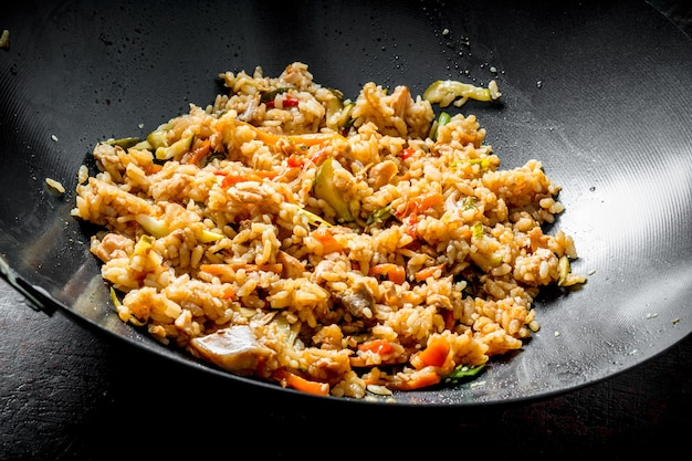 Chinese wok. rice with beef and vegetables on wooden table