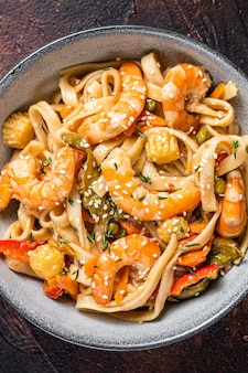 Chinese wok stir-fry udon seafood noodles with shrimp prawns in a bowl. black