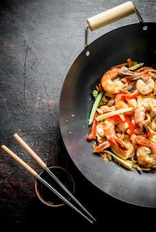 중국 냄비. 어두운 시골 풍 테이블에 젓가락과 간장을 곁들인 냄비 냄비에 우동