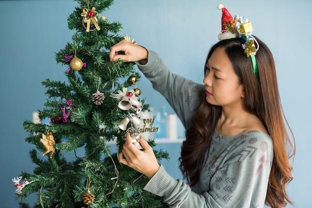 クリスマスツリーを飾る中国の女性