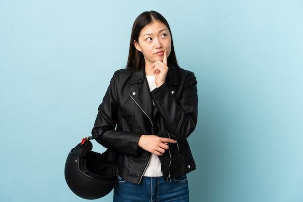 アイデアを考えて孤立したオートバイのヘルメットを保持している中国の女性