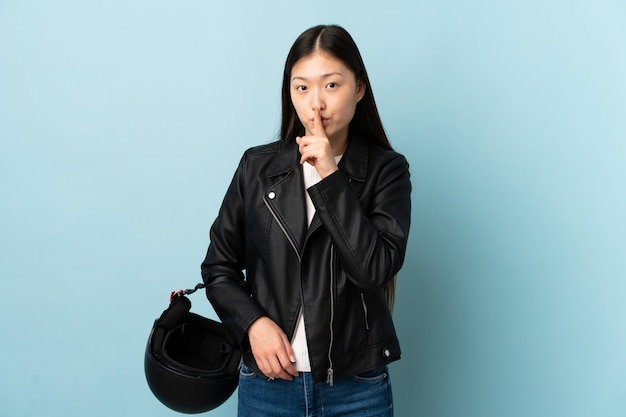 Китайская женщина, держащая мотоциклетный шлем над синим, делает жест молчания