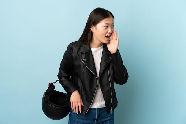 파란색 입 벌리고 외치는 동안 오토바이 헬멧을 들고 중국 여자