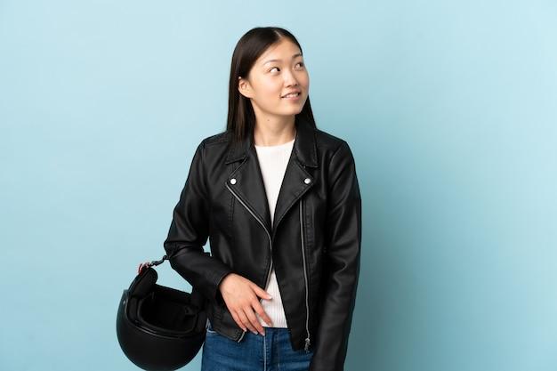 격리 된 파란색 배경 위에 오토바이 헬멧을 들고 중국 여자 웃음과 찾고