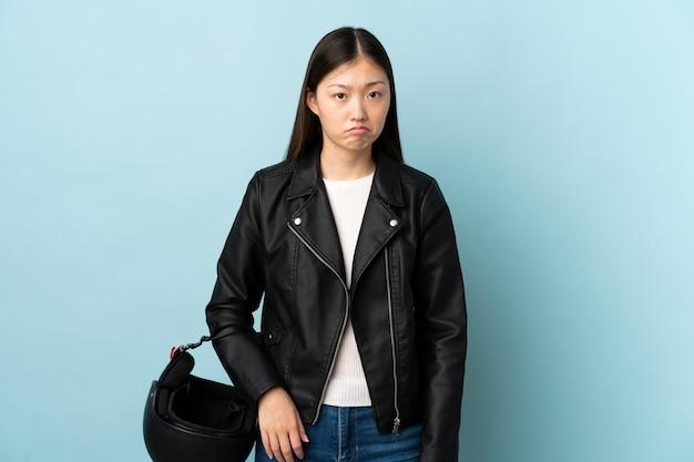 悲しい孤立した青い背景の上にオートバイのヘルメットを保持している中国の女性