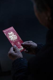 中国の旧正月の願いと伝統的な赤い封筒を保持している中国の女性