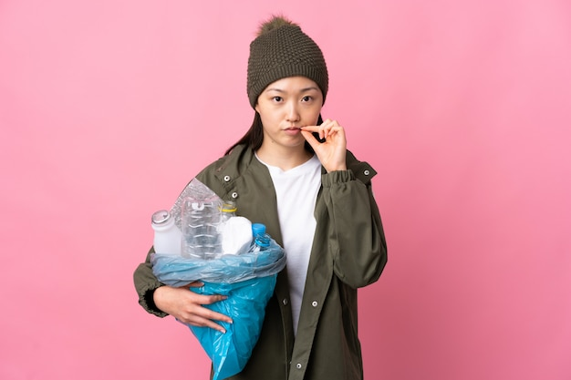 Chinese woman holding a bag full of plastic bottles to recycle over isolated pink wall showing a sign of silence gesture